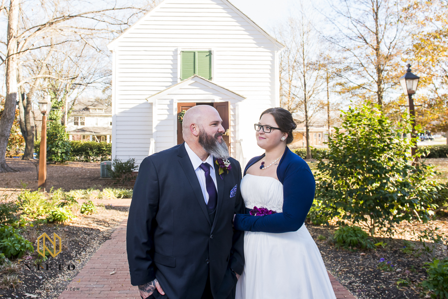 bride and groom smiling at each other nicely as they pose in mordecai historic park in front of St. Mark's Chapel