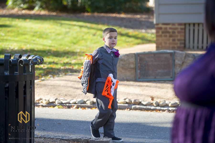 ring bearer with a nerf gun on his hip as he walks around Mordecai Historic Park