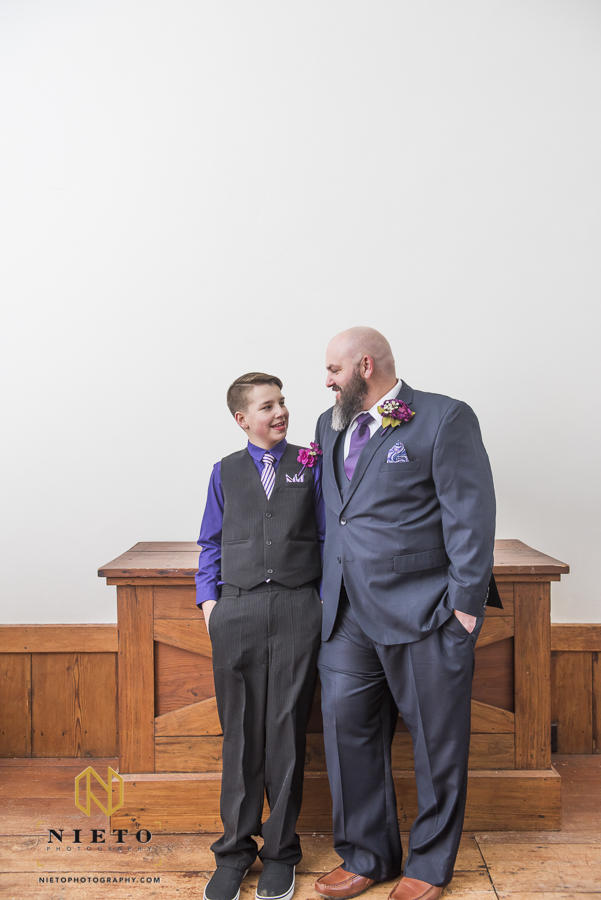 groom and his oldest son looking at each other and smiling