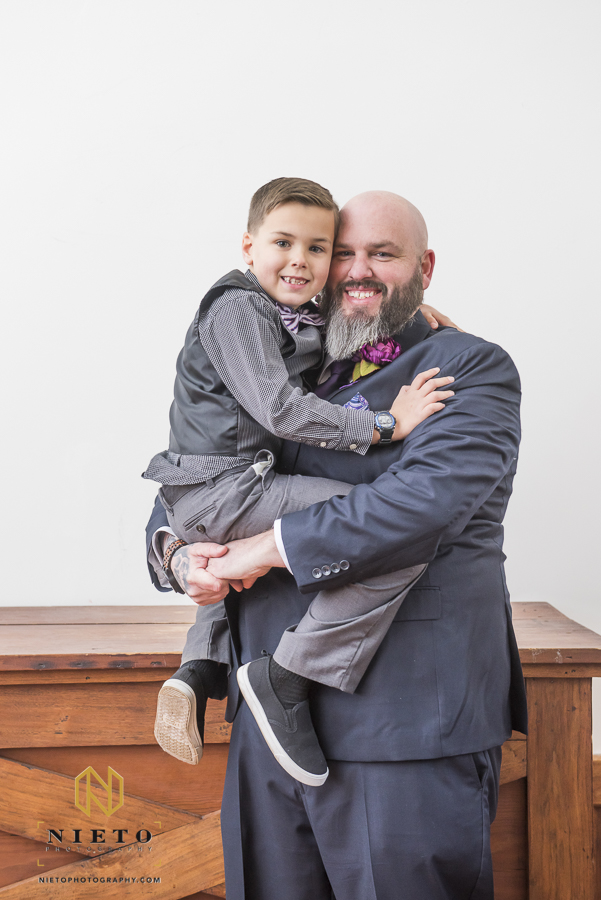 groom holding his youngest son in his arms and both are smiling for the camera