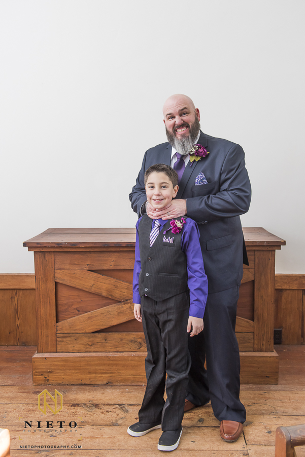 groom pretending to choke his son while posing for a portrait inside of St. Mark's Chapel