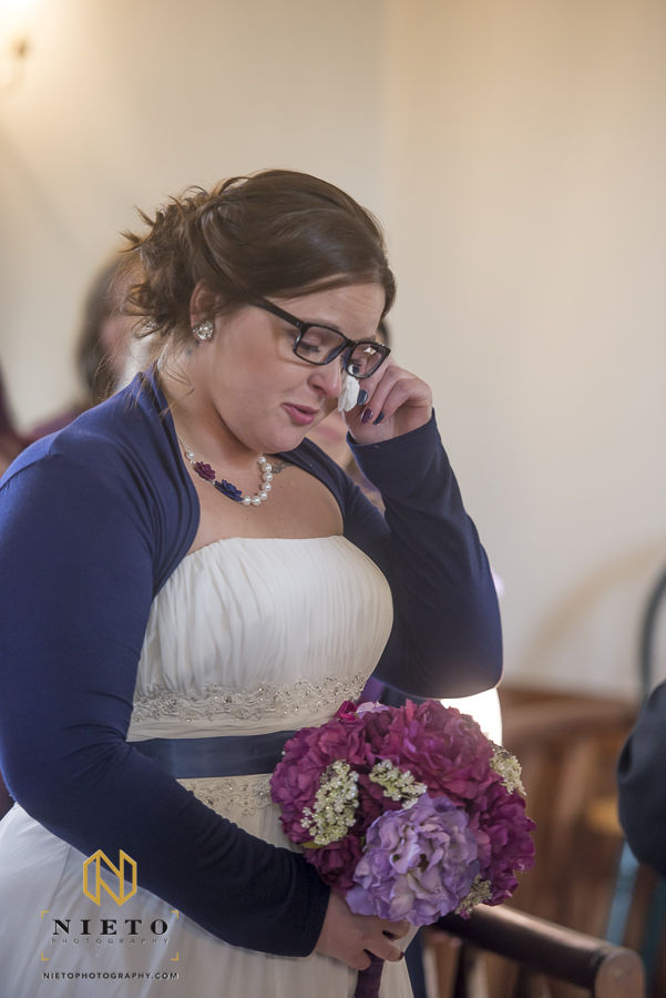 the bride whipping tears from her eye with a tissue during her ceremony