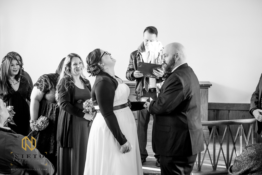 black and white image of bride laughing as the groom tries to place the ring on her finger