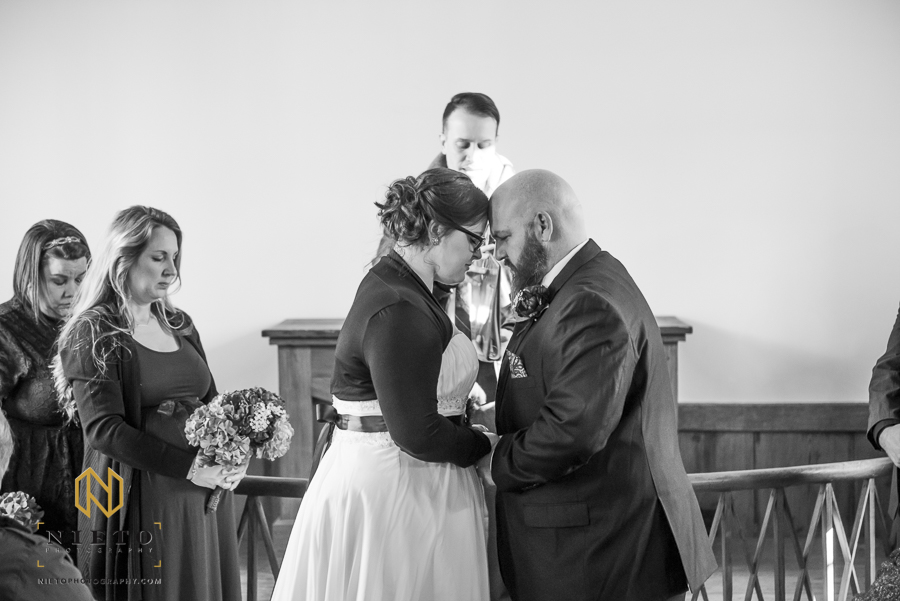 Black and white image of bride and groom praying and leaning foreheads into each other