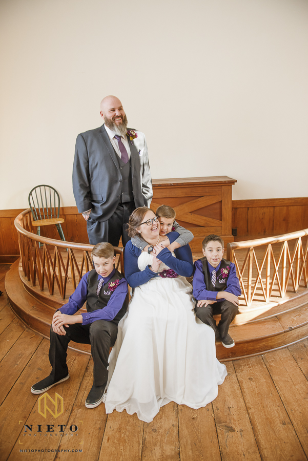 bride sitting and laughing while being hugged by a little boy with the groom standing behind her laughing