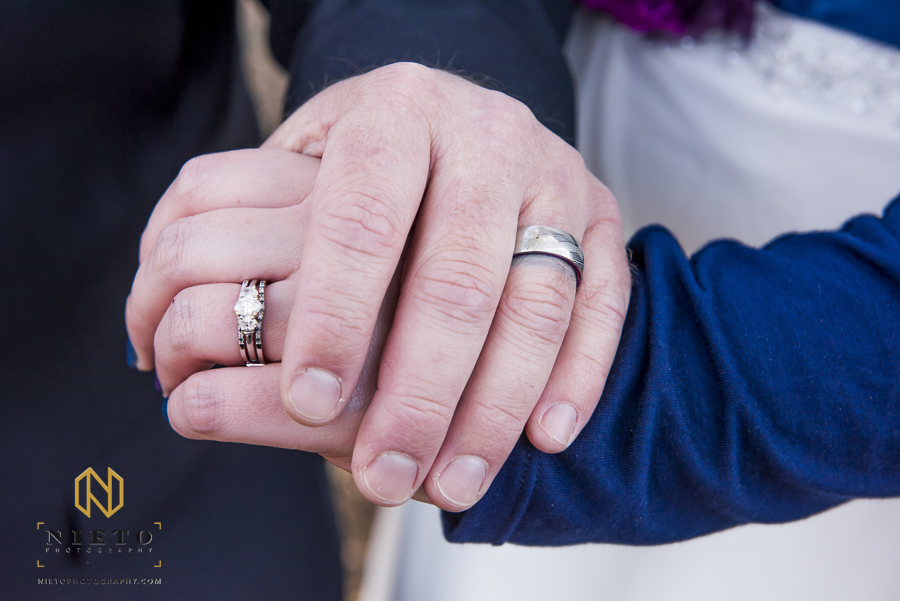grooms hand on top of the brides hand to show off their wedding bands