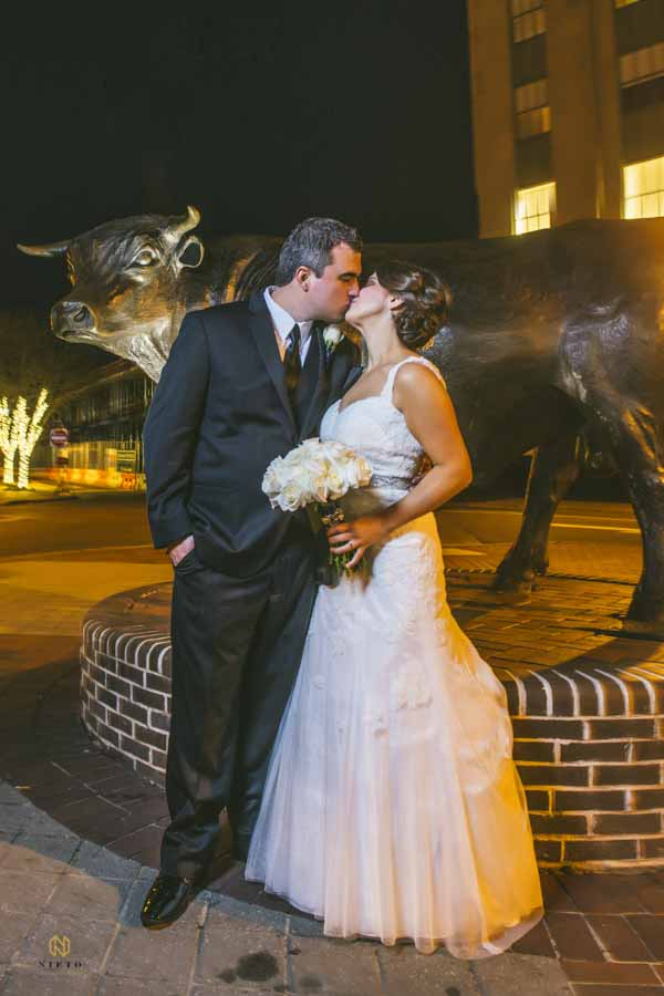 bride and groom kissing in front of a bull statue in Durham, NC at night