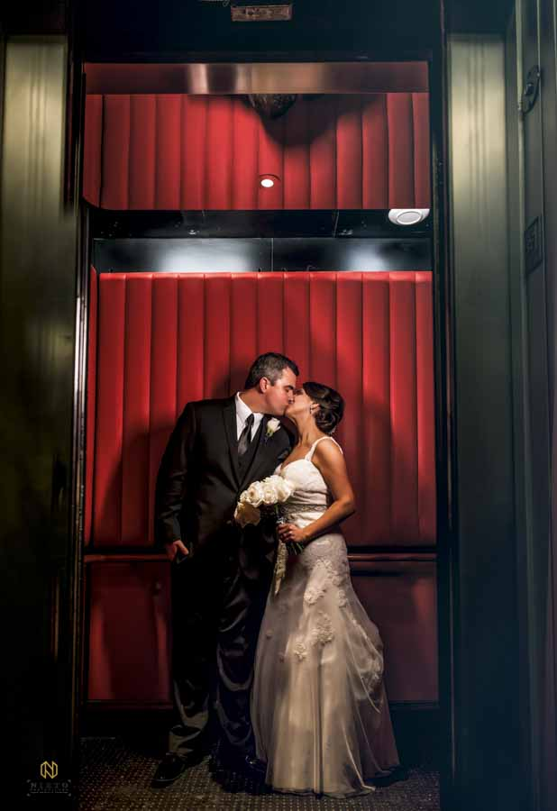 couple kissing in the red elevator at 21C Hotel in Durham