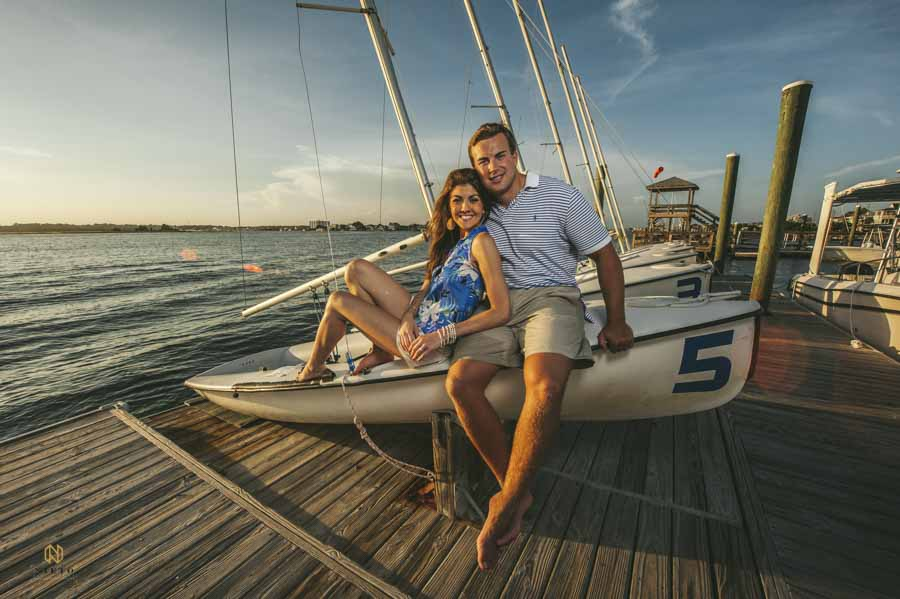 Couple sitting on docked sail boat at sunset in wrightsville nc
