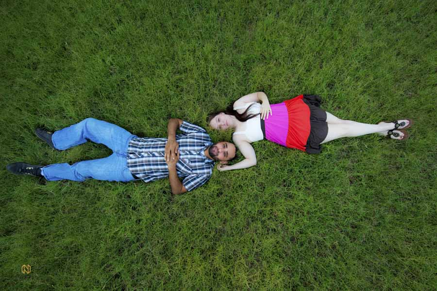 overhead shot of couple laying in grass posing for their raleigh engagement portraits