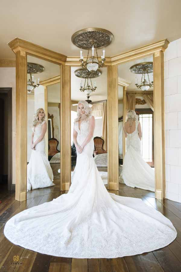 bride standing with her wedding gown spread around her in front of three mirrors