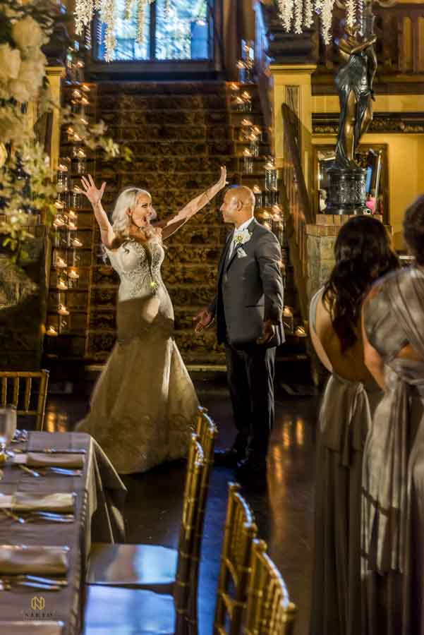 The bride smiling and her hands in the air as she and her husband are announced for the first time at their Barclay Villa wedding reception