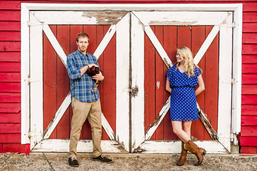couple posing against barn doors while the man holds a chicken