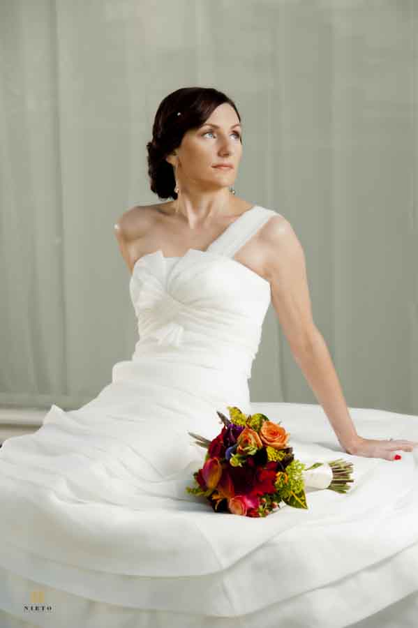 bride sitting at the NCMA posing for her raleigh bridal portraits with a bouquet in her lap