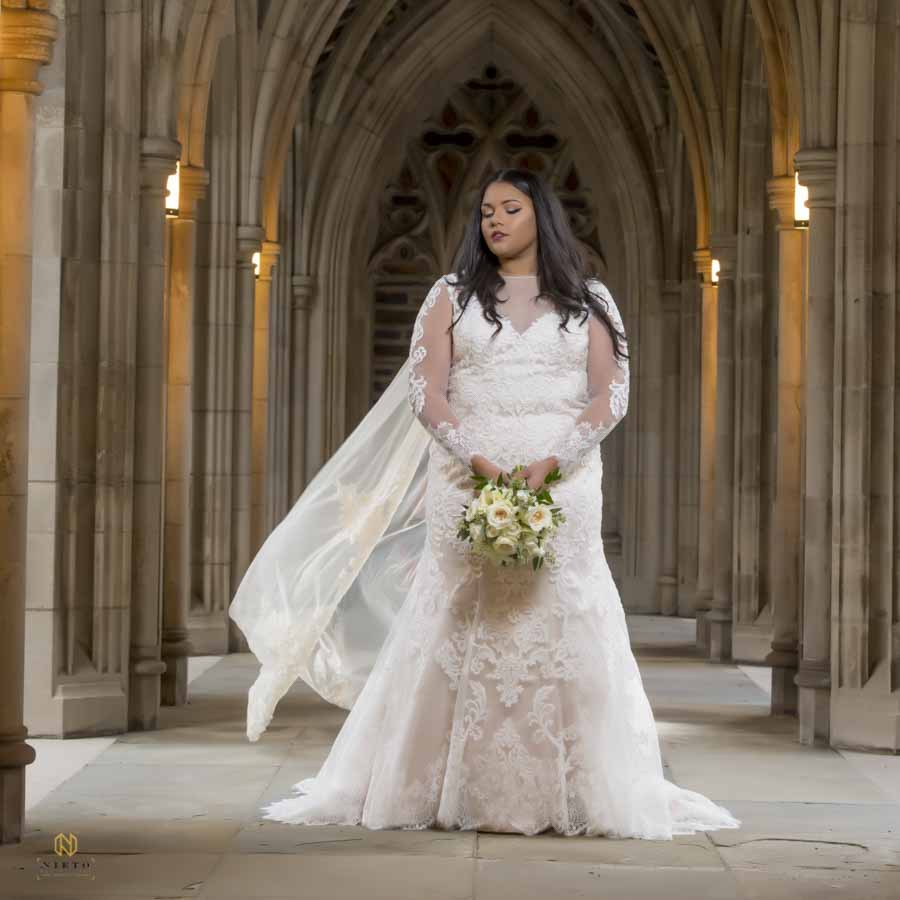 bride in the hall way at duke chapel posing for her bridal portrait with her floral bouquet.