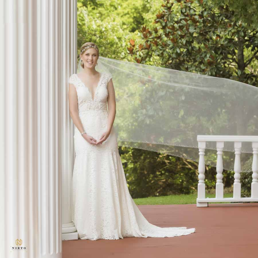 Bride smiling as her veil blows in the wind on the front porch of the Garden on Millbrook