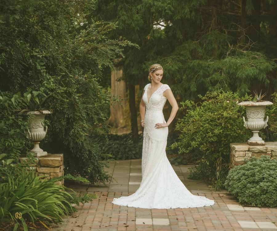 Bride posing for her raleigh bridal portraits in the white garden of JC Raulston Arboretum