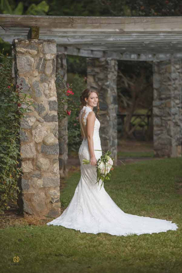 Bride standing in the raleigh rose garden smiling while holding her bridal bouquet