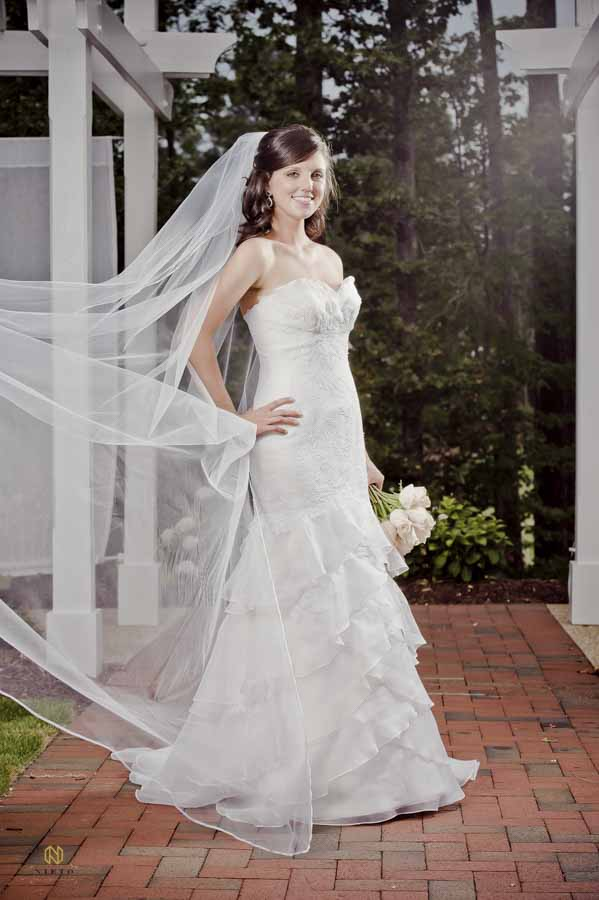 bride standing with her hand on her hip as she smiles posing for her Raleigh bridal portrait