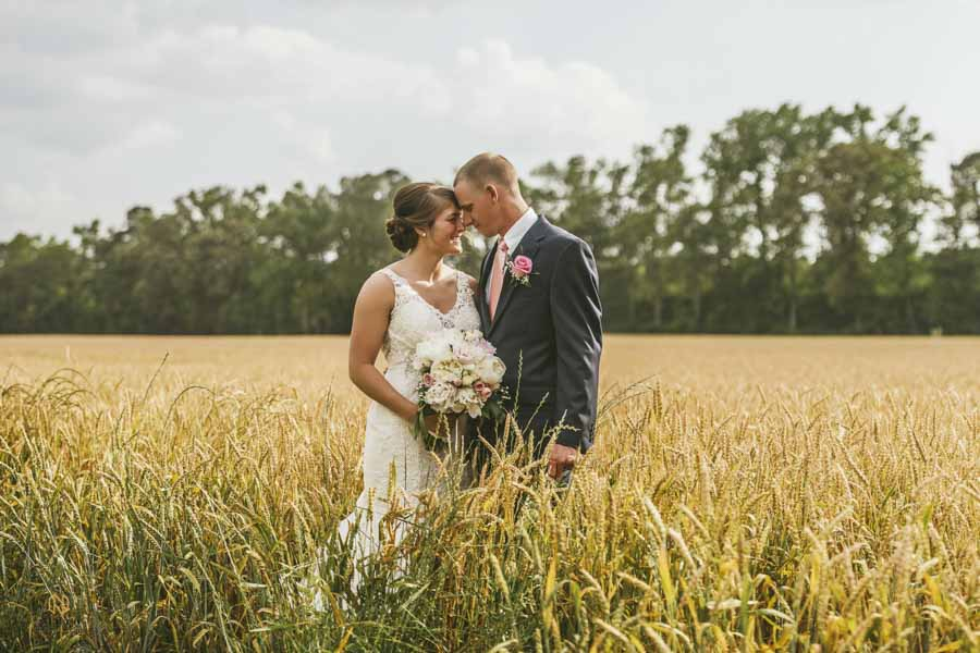 couple leaning heads into each other while standing in a wheat field
