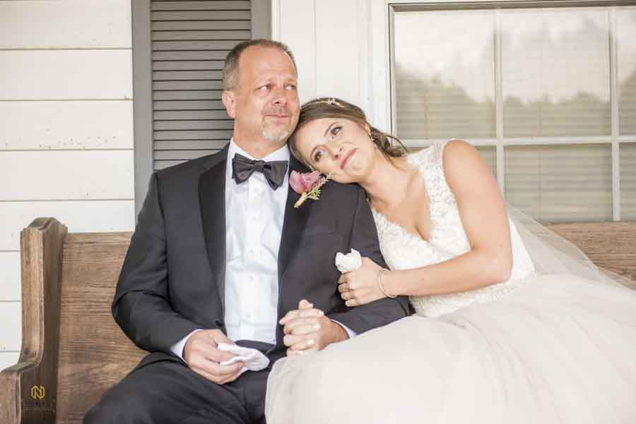 bride and her father crying as the sit beside each other on the porch at Cedar Grove Acres