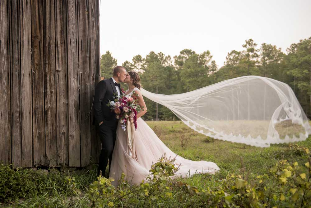 Bride and groom outdoors next to a barn at Cedar Grove Acres posing for their Raleigh Wedding Photographer