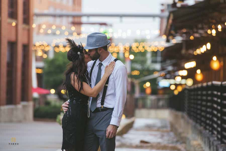 A couple kissing while dressed in 1920s clothing during their engagement session at the American Tobacco Campus