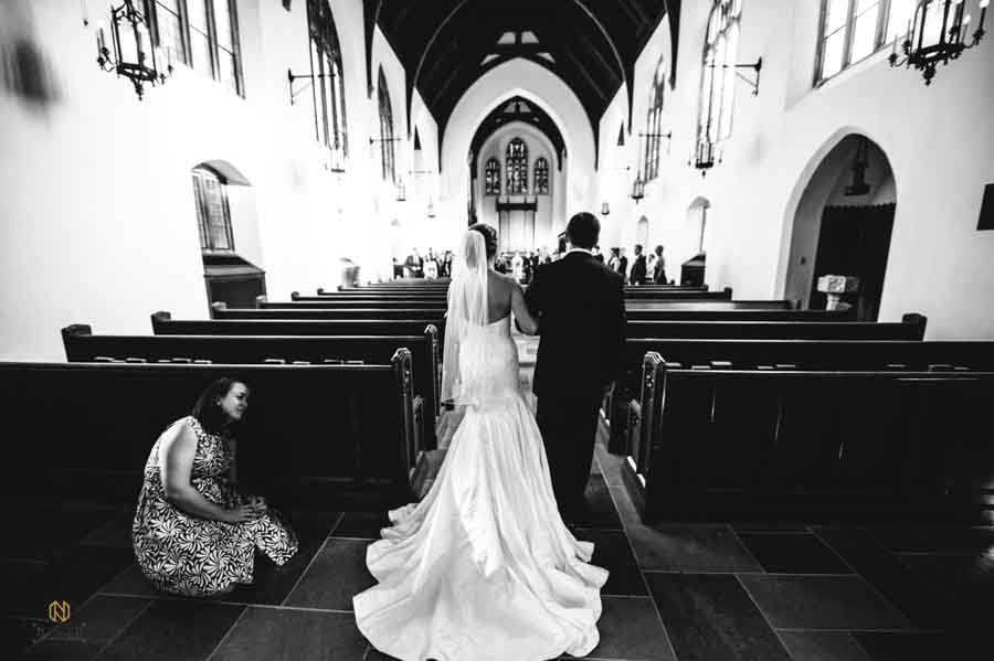 black and white image of the bride and her father walking down the aisle as the church lady hides behind the bench to get out of the picture