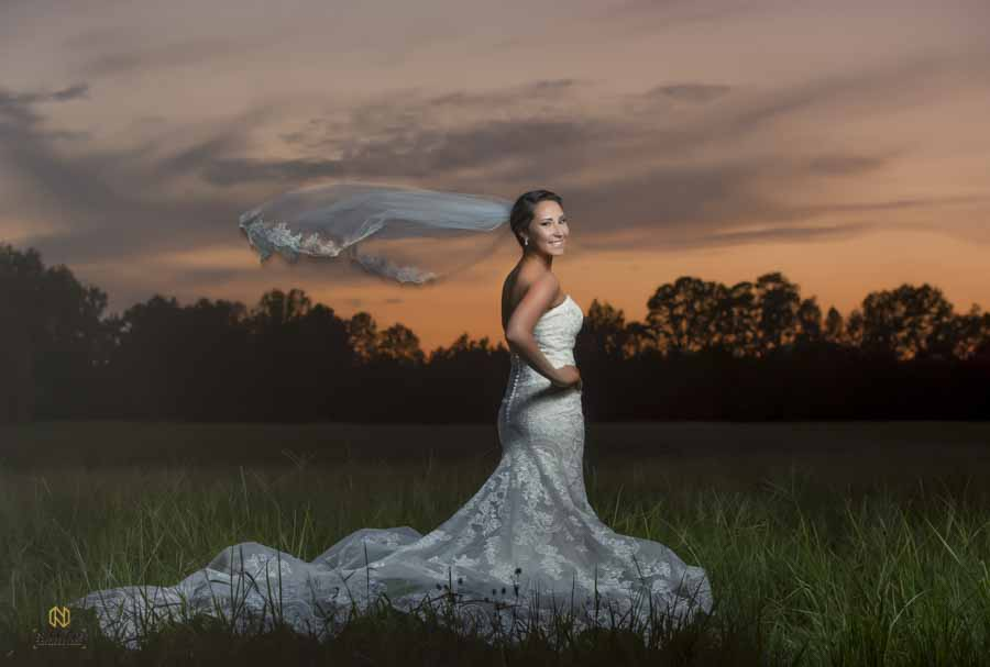 Bride posing for her portrait at sunset with her veil blowing in the wind