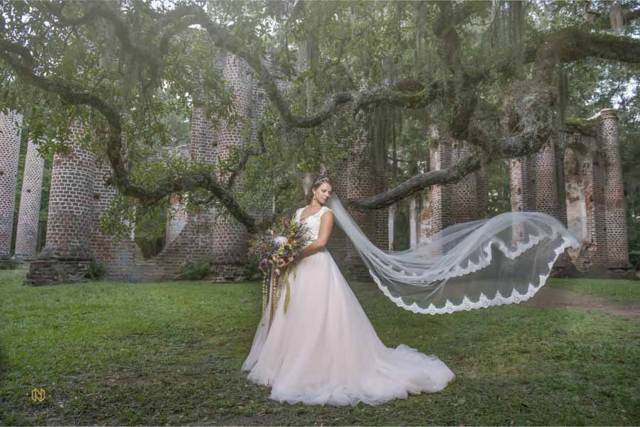 bride standing in front of old church ruins looking over her shoulder as her veil blows in the wind