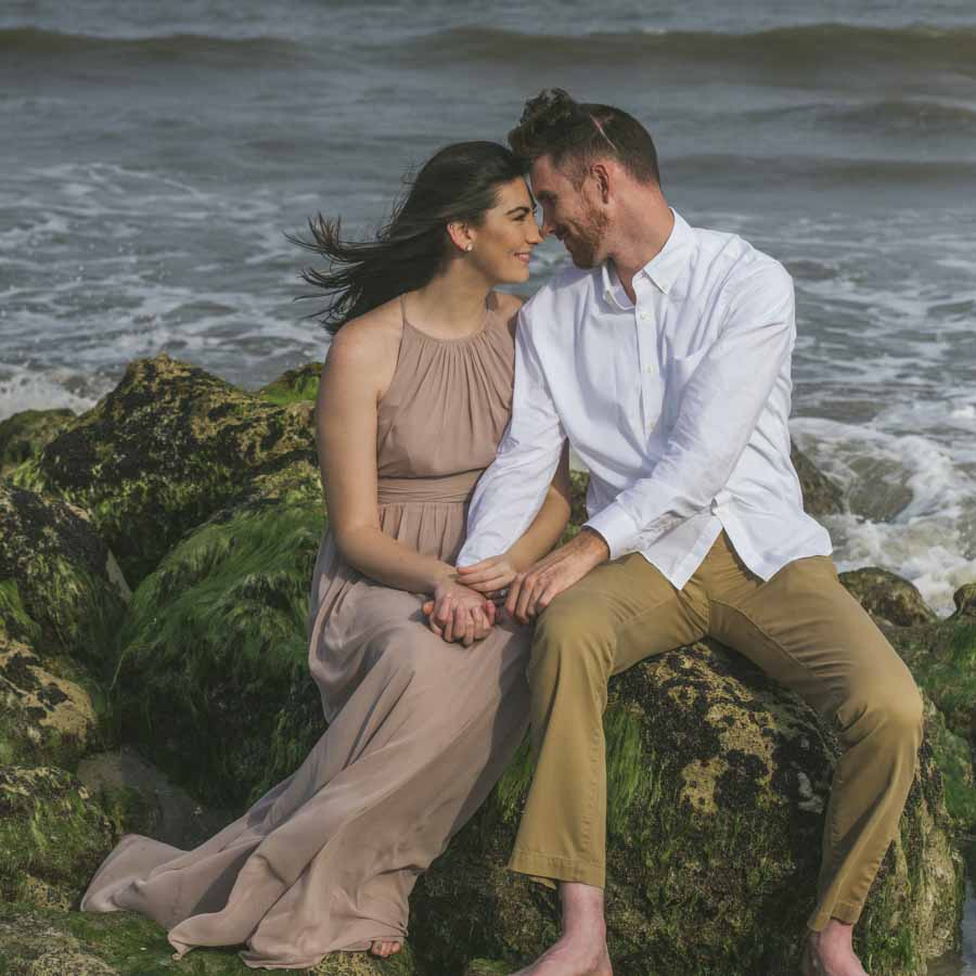engagement session at Kure Beach on the green rocks and the ocean in the background
