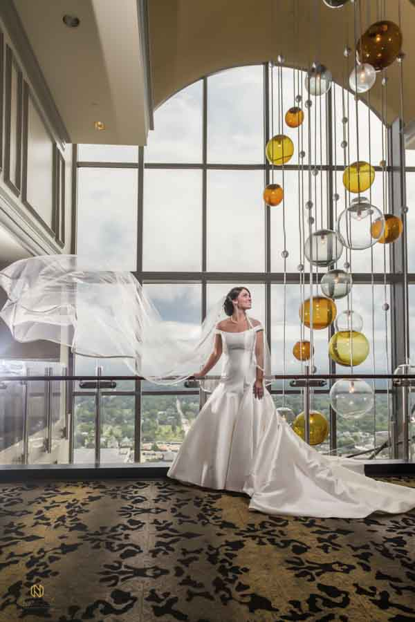 Bride looking at lighting fixture while her floats in the air at City Club Raleigh