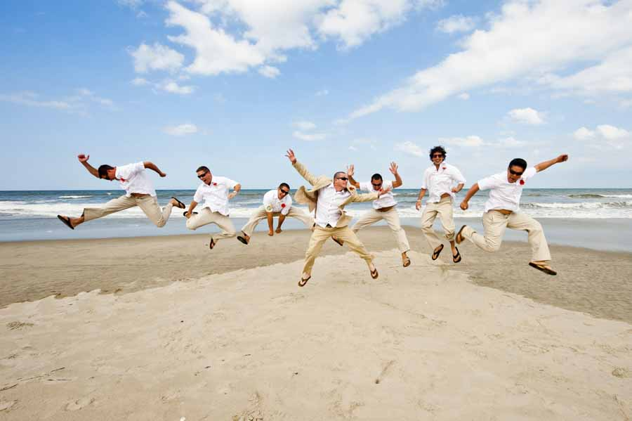 Groom and his groomsmen jumping on the beach in Coralla OBX for their Raleigh Wedding Photographer