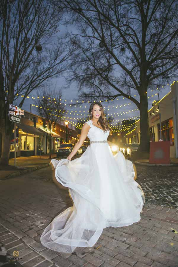 bride dancing in her wedding dress on the road outside of Market Hall