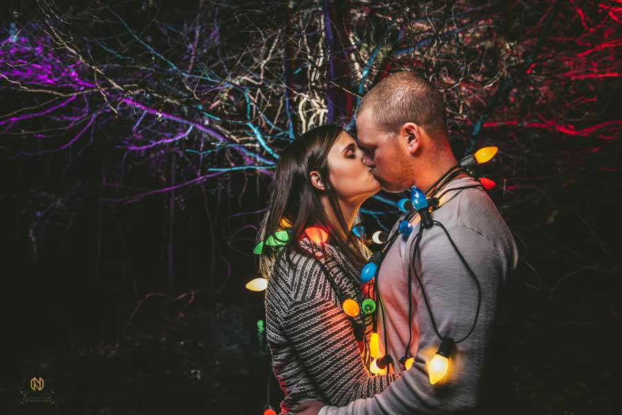 couple kissing in the woods at night with vintage christmas lights around their body