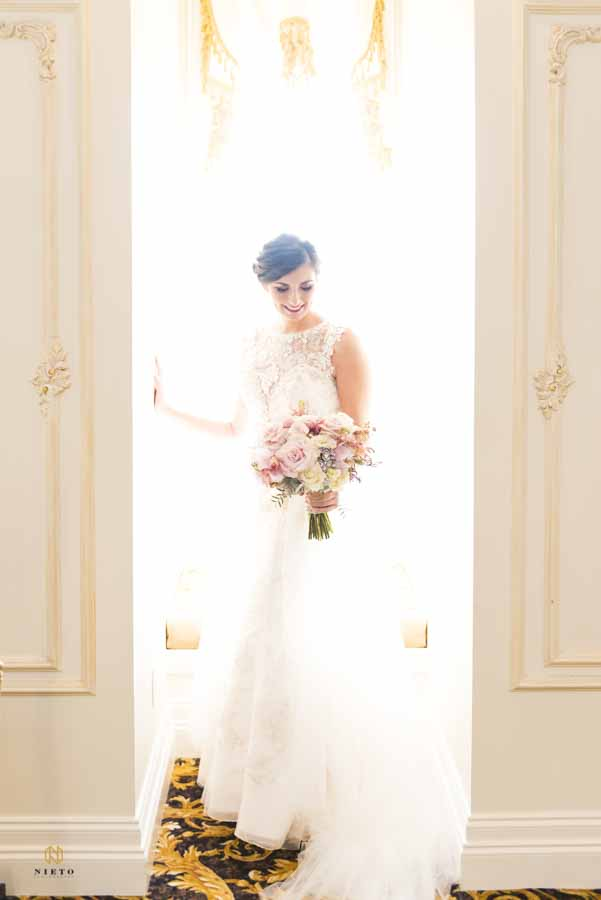 bride standing in front of a window admiring her bridal bouquet at the Landmark