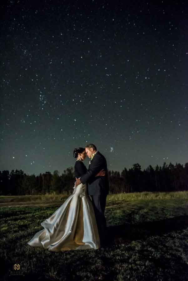 couple hugging and touching foreheads while standing in field on a starry night
