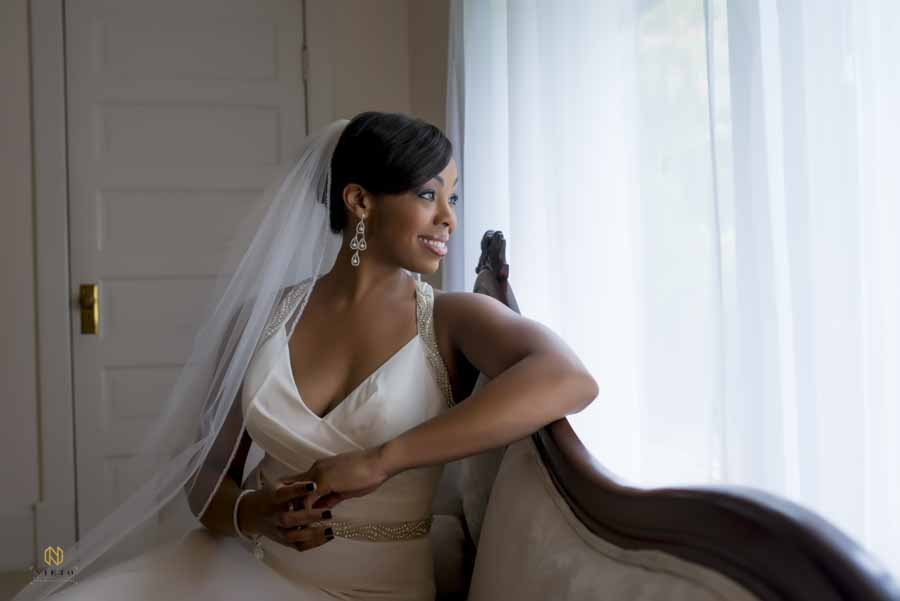 Bride leaning on a lounge chair smiling as she looks out a window at the Hudson Manor