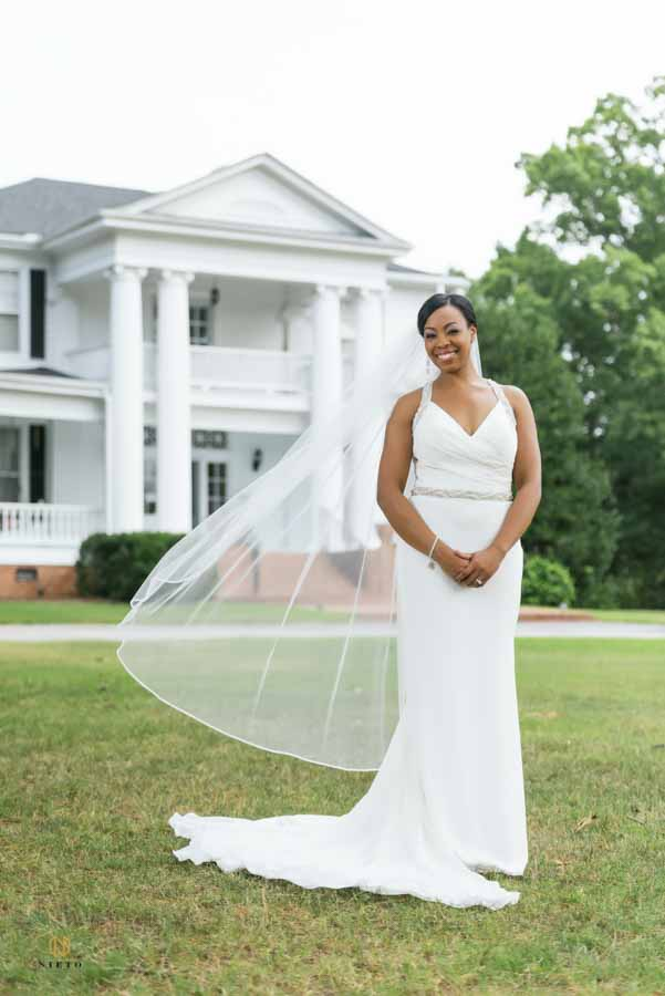 bride smiling as she stands in front of The Hudson Manor with her veil blowing in the wind