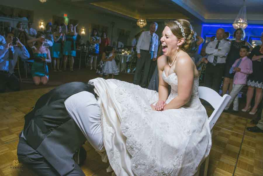 Bride laughing as the groom has his head under her dress trying to remove her garter at their Hudson Manor wedding reception