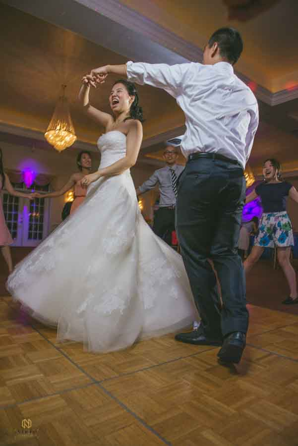 photo of bride smiling and twirling while dancing with groom at the Hudson Manor
