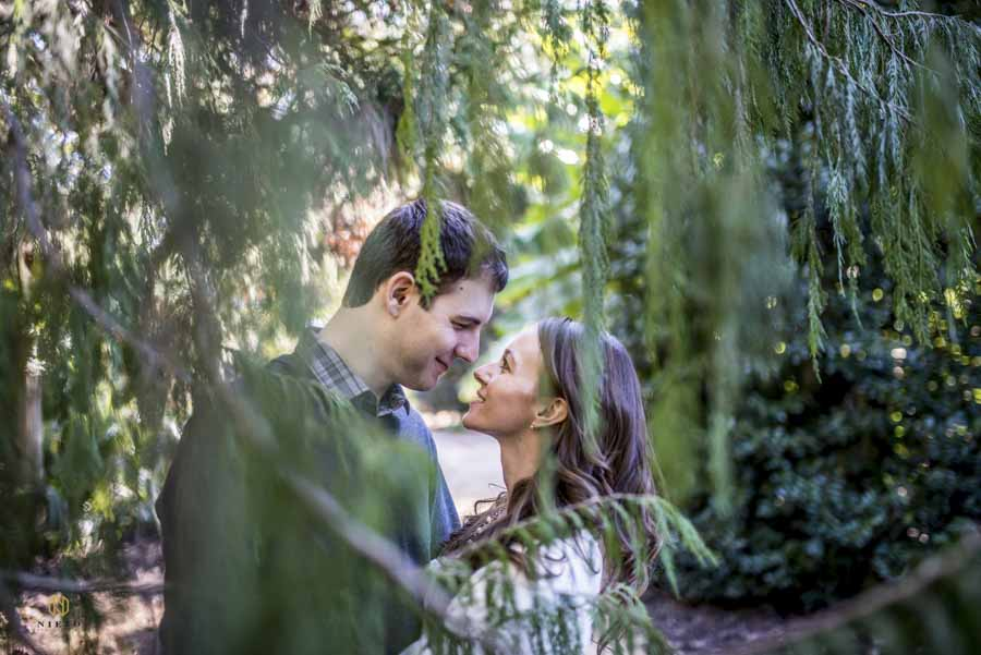 couple smiling at each other under a fir tree at JC Raulston arboretum