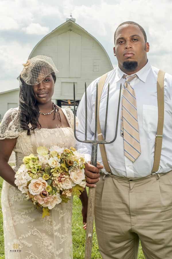 Bride and Groom posing in front of barn to recreate American Gothic portrait
