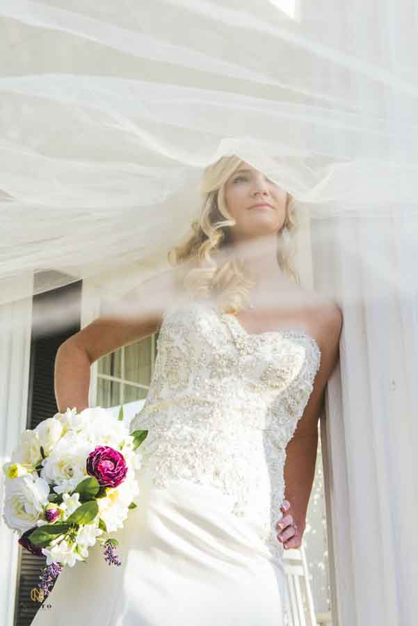 Julie leaning against while column on the porch of the Hudson Manor with her veil blowing in the wind