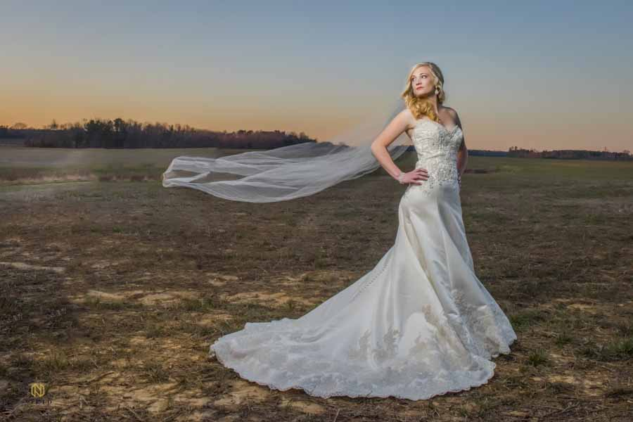 Bride in a field posing for her Raleigh bridal portrait as her veil blows in the wind behind her