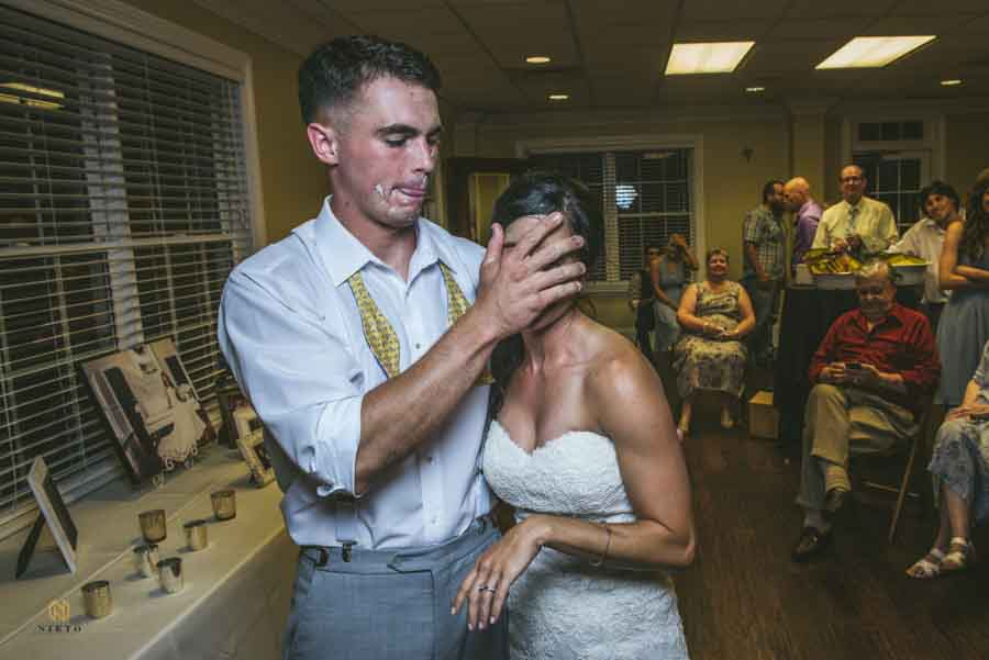 groom smashing wedding cake in the brides face at River Ridge Golf Club