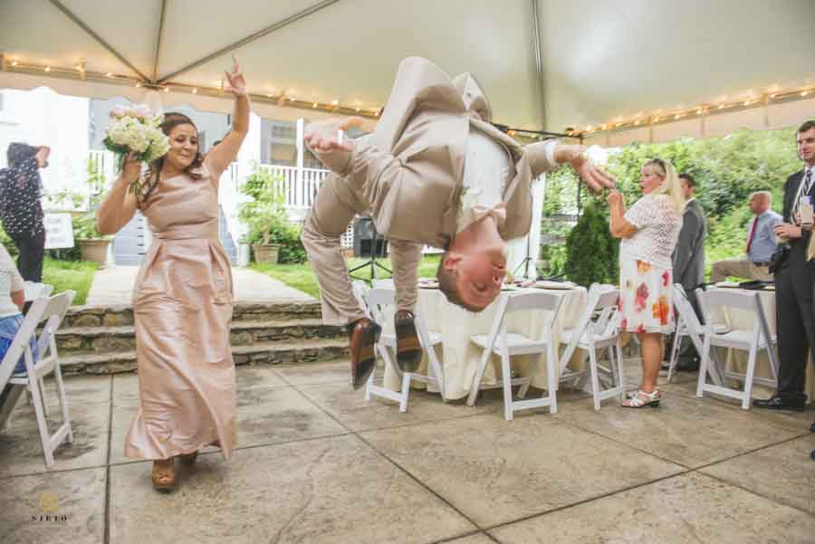 groomsman doing a backflip during his intro to the wedding reception