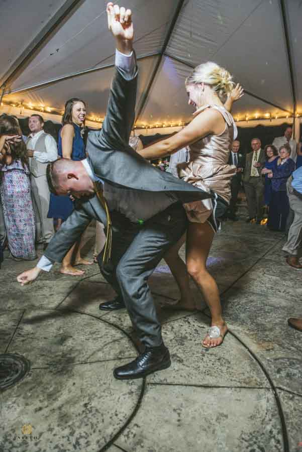 groomsman and bridesmaid dancing widely on the dance floor