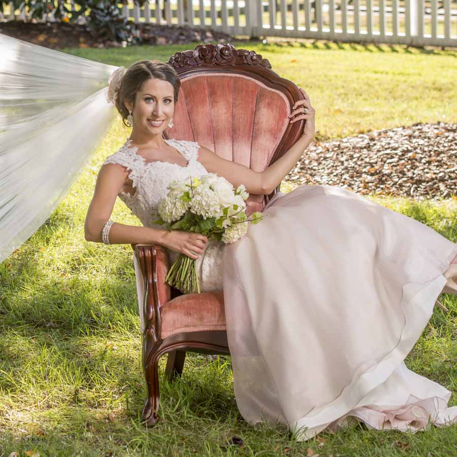 Bride sitting in a chair smiling as her veil blows in the wind on the front lawn of Lake O the Woods