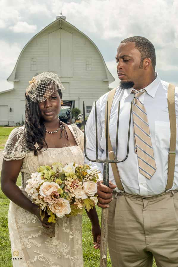 Bride and Groom posing in front of barn as the groom looks at the bride disapprovingly